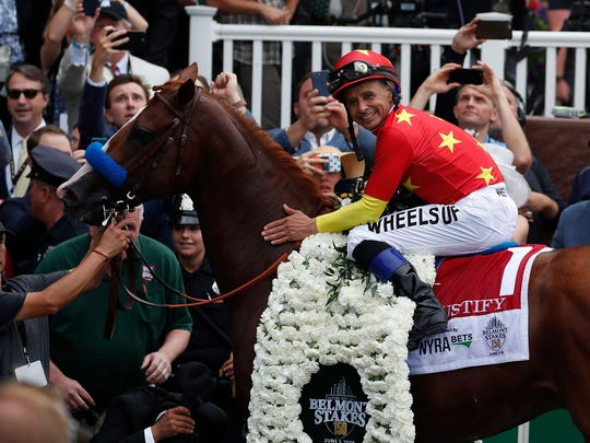 Mike Smith, aboard Justify, poses for photos in the winner circle after winning the 150th Belmont Stakes to become the 13th Triple Crown winner.