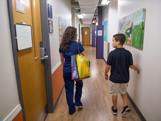 Sam Blackwood, 9, walks down a hallway with his occupational therapist, Kelly MacIntire, at Kidnetics in Greenville on Tuesday, June 19, 2018.