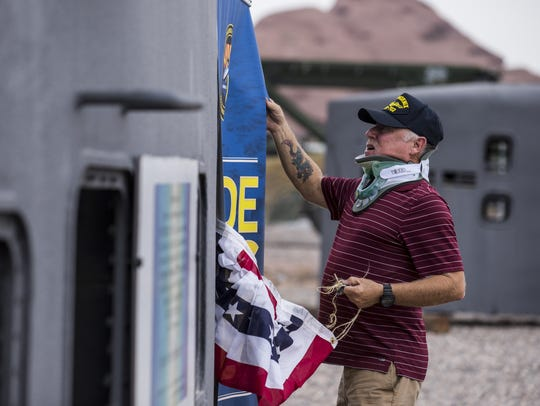 Tom Solnit removes a banner after a reunion for veterans