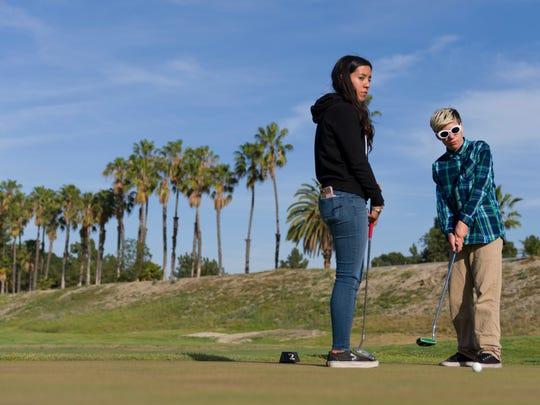 Andrea Pena, 14, (left) watches as Carson Fullerton,