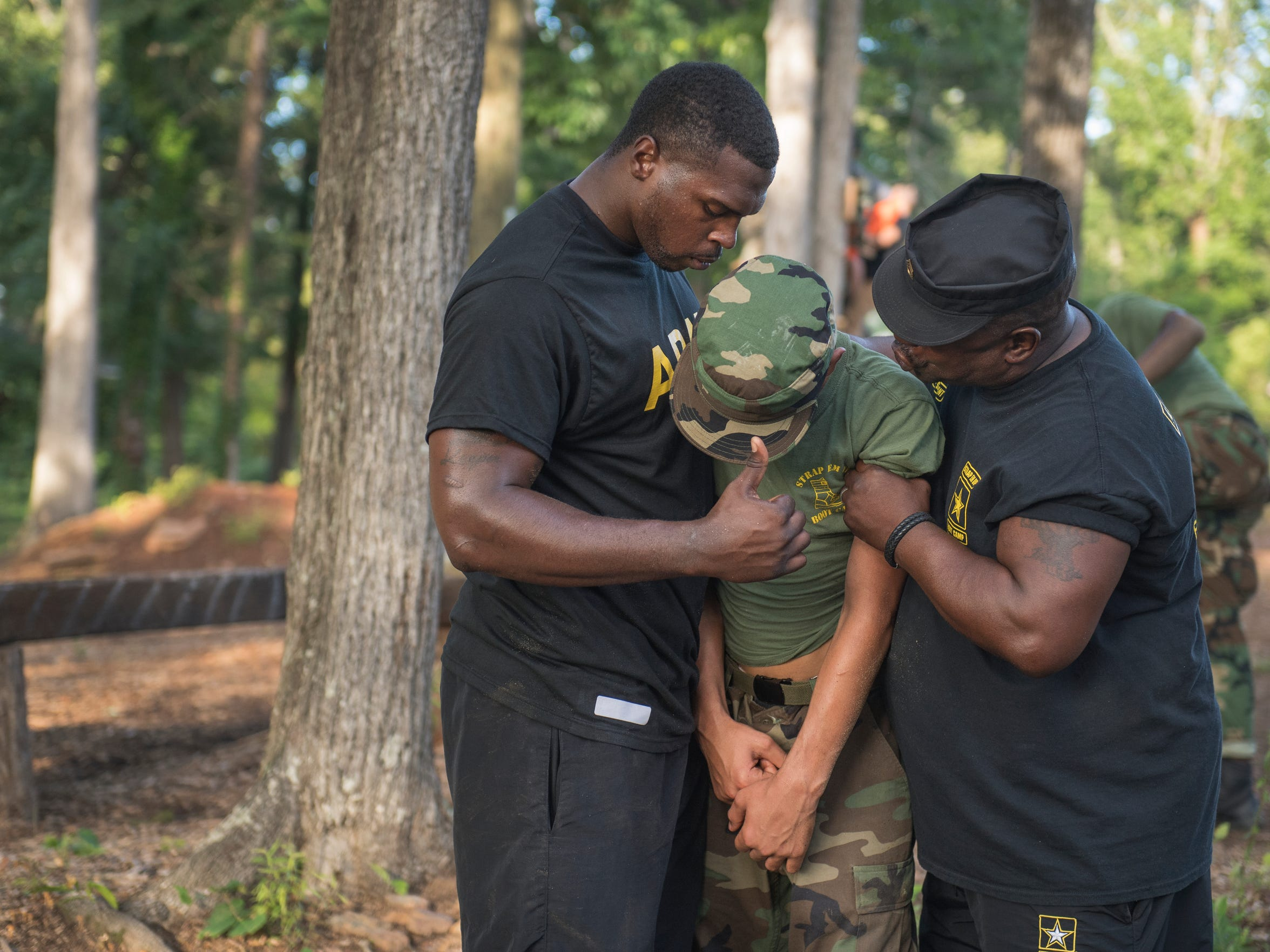 Martin Gabriel, 14, is held up by Sergeant Kenneth Pitts and Drill Sergeant Steven Sullivan as he breaks down after doing push ups on Tuesday, May 22, 2018.