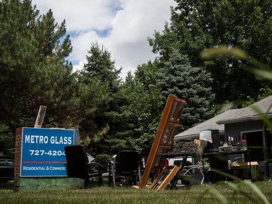 Office supplies and furniture from inside Metro Glass sit in the front lawn as clean up is underway on Sunday, July 1, 2018, in Clive, after flash flooding surrounded the building the night before.