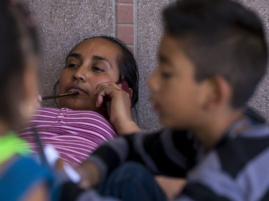 Guadalupe Arcos Avila, 34, a migrant from the state of Guerrero, talks on the phone on Thursday, June 21, 2018, at the DeConcini Port of Entry in Nogales, Sonora, Mexico. Fifty-six families in Nogales are waiting to apply for asylum.