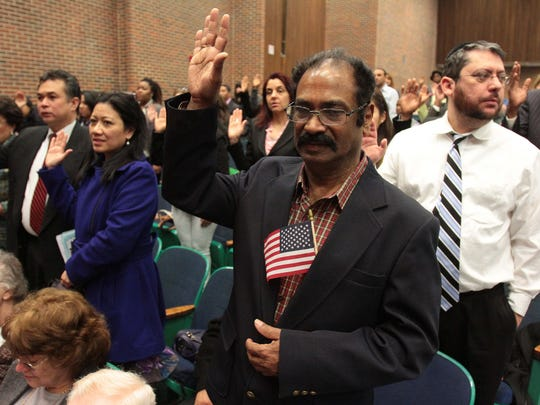 Rajan Daniel, center, of Congers takes the oath of