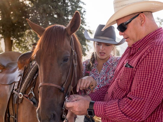 Joe Stewart, right, helps his daughter Lizzie Stewart adjust the bridle on Dennis before competition at the Woodlake Rodeo Grounds on Saturday, July 7, 2018. Lizzie and her Quarter Horse won the 2018 State Barrel Racing Championship and are headed to nationals in Wyoming this month.