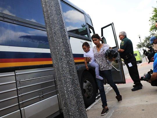 Mujeres provenientes de Honduras descienden a de una autobús de inmigración.