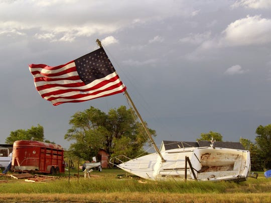 A powerful storm in northeastern Montana left this boat tilted with a flag still standing on its mast after a thunderstorm in Plentywood, Mont.
