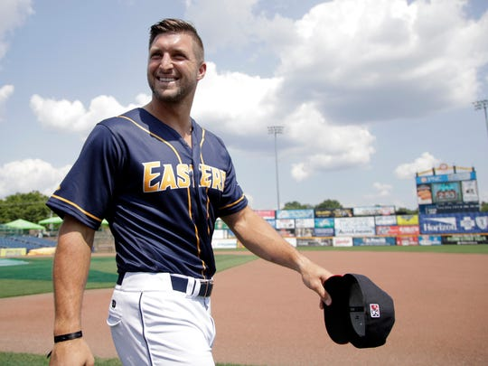 Tim Tebow walks on the field before the Class AA Eastern