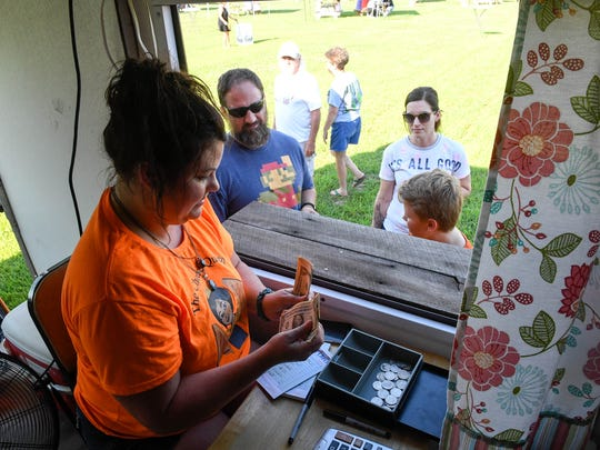 Candice Hughes works the window at The Cheese Queen food truck during the Food Trucks at the Farm event hosted by the Evansville Food Truck Association at Farm 57 every Wednesday, July 11, 2018.