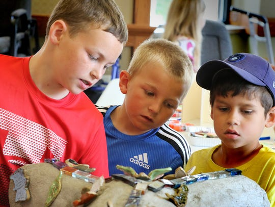 Charlie Hackel (left), Brady Hackel and Johnathan Grooms of the Summit View Elementary School's SHARP Literacy program in July 2018 checked the progress of applying ceramic butterflies to a concrete tree that was to be installed at Shorehaven. Summit View was recently named a 2019 National Magnet School of Distinction by Magnet Schools of America.