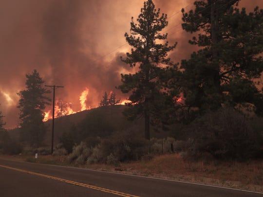 The Cranston Fire burns near Highway 74 between Mountain
