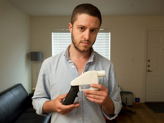 Cody Wilson, the founder of Defense Distributed, shows a plastic handgun made on a 3D printer at his home in Austin, Texas.