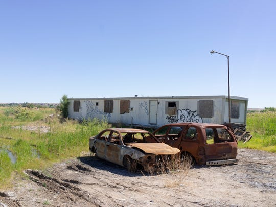 A mobile home and burned-out cars in the Navajo Nation