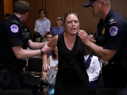 U.S. Capitol Police remove a protester from the hearing