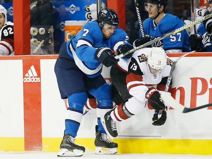 Winnipeg Jets' Ben Chiarot (7) checks Arizona Coyotes'