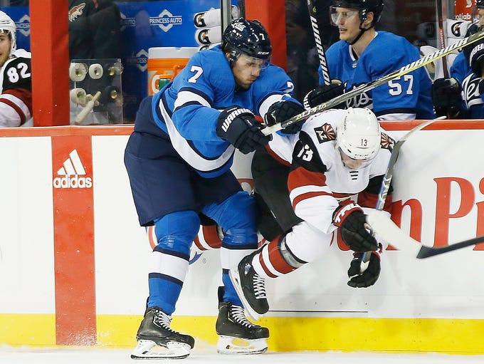 Winnipeg Jets' Ben Chiarot (7) checks Arizona Coyotes'