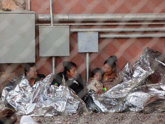 Migrants held in temporary fencing underneath the Paso