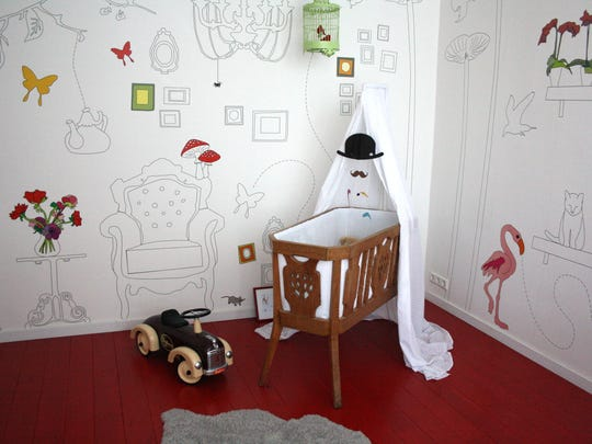 Rich red paint on the hardwood floor brings warmth and color to this stylish, gender-neutral nursery. Painting hardwood floors can be an inexpensive and easy solution, especially in rooms where the floors has become worn and scuffed after many years of use. ()
