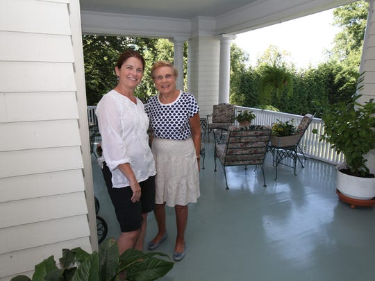 Maria Stanton stands Aug. 25, 2014 with her mother Paula DelGuercio on the front porch at White Cottage, an historic estate on the Long Island Sound in Larchmont.