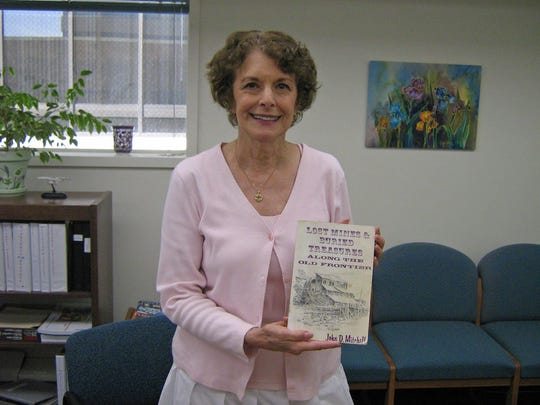 Bonnie Saviers in 2008 with the Washoe County Library System poses with a book that was returned way past the grace period: It was checked out for 10 years.