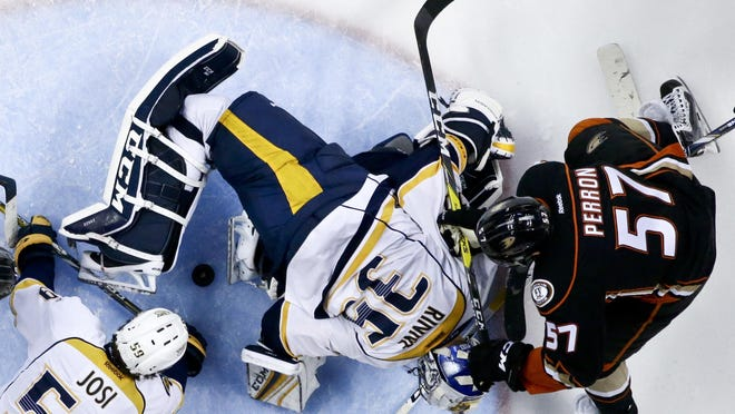 Nashville Predators goalie Pekka Rinne, middle, blocks a shot by Anaheim Ducks left wing David Perron, right, as defenseman Roman Josi helps Rinne during the third period of Game 7 on April 27, 2016. The Predators won 2-1.