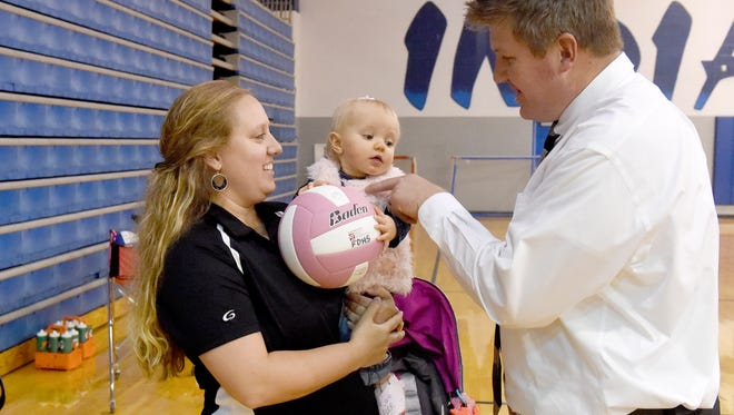 Wendy Hull holds one-year-old daughter, Sawyer Hull, as husband and father Brent Hull plays with their child. They wait for the start of the evening's varsity volleyball match at Fort Defiance High School on Tuesday, Oct. 11, 2016. Wendy currently serves as the assistant coach of Fort Defiance's varsity volleyball team while Brent is a teacher at the school.
