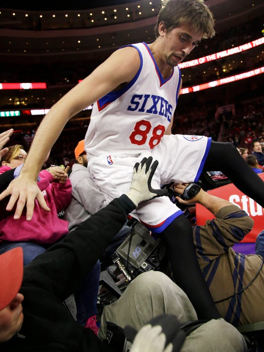 Philadelphia 76ers' Alexey Shved, of Russia, falls into a television crew after chasing a loose ball during the first half of an NBA basketball game against the Boston Celtics, Monday, Dec. 15, 2014, in Philadelphia. (AP Photo/Matt Slocum)