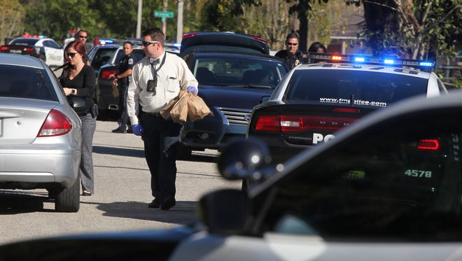 Members of the Fort Myers Police Department investigate the scene of a drive-by shooting on Sunday.