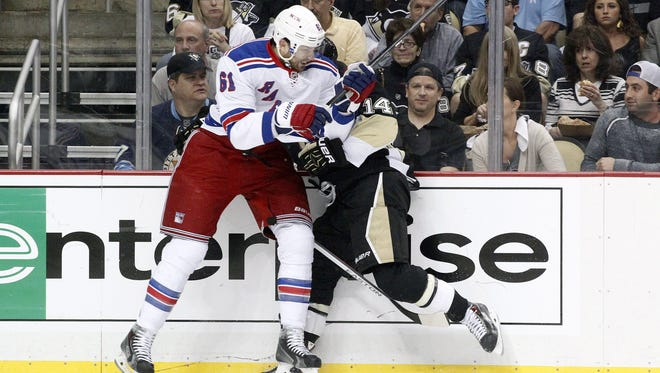 Rangers left wing Rick Nash, left, checks Penguins left wing Chris Kunitz during the first period Tuesday.