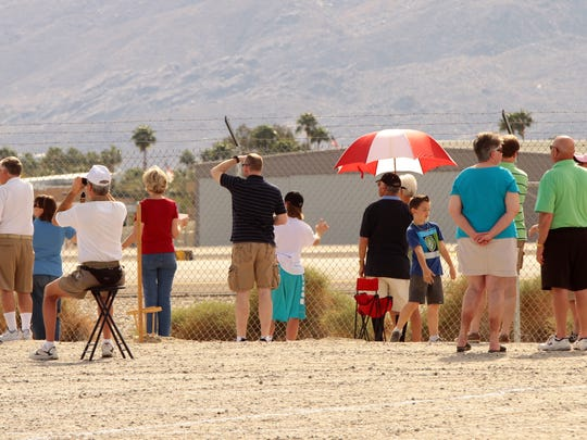 People wait at a Palm Springs Air Museum parking lot to watch Air Force One take off on  Feb. 17, 2014, at Palm Springs International Airport in Palm Springs after a four-day trip by President Barack Obama to the area.