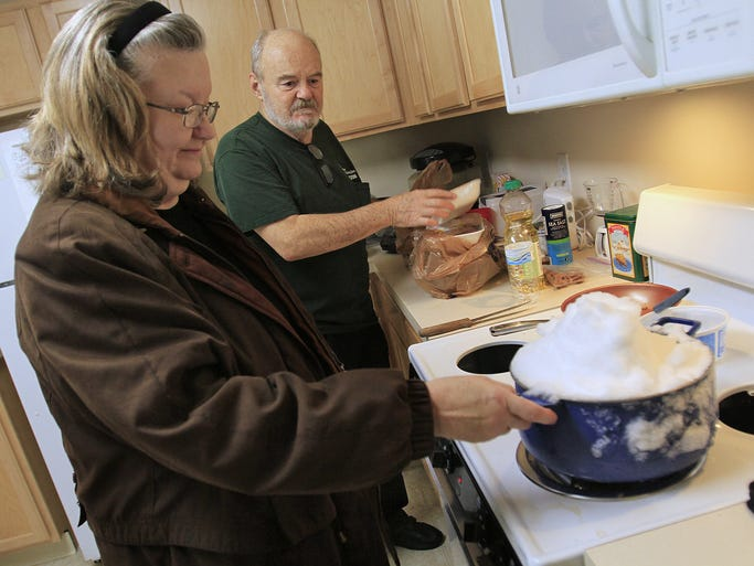 Connie Thomas, left, melts a pot of snow to put in her toilet tank to flush the toilet, as her boyfriend and roommate Lynn McQuairn puts away groceries at Benjamin Court Apartments, Wednesday, January 8, 2014.  Residents reported to being without water since a pipe break on Monday, when water was turned off.  Flushing toilets, washing hands, washing dishes, and even maneuvering around the complex because of slick sidewalks were problems.