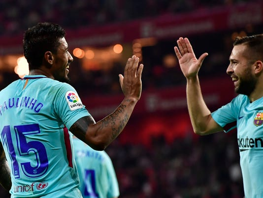 FC Barcelona's Paulinho Bezerra, left, celebrates his goal with teammate Jordi Alba after scoring against Athletic Bilbao during the Spanish La Liga soccer match between Athletic Bilbao and FC Barcelona, at San Mames stadium, in Bilbao, northern Spain, Saturday, Oct. 28, 2017. FC Barcelona won the match 2-0. (AP Photo/Alvaro Barrientos)