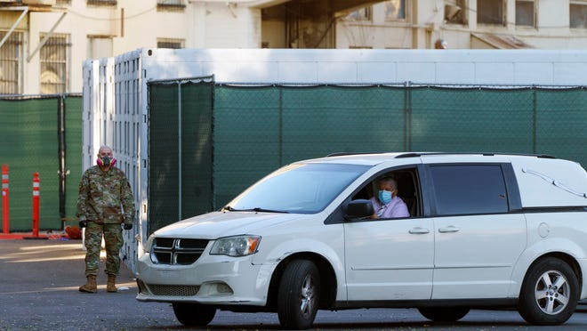 A member of the California National Guard stands next to refrigerated trailers as a funeral hearse driver exits the department of the Los Angeles County Coroner on Monday.