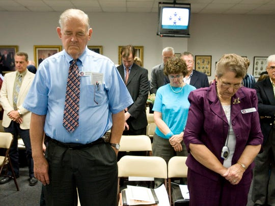 Anthony Bruner and Mary Lou Bruner, right, pray at