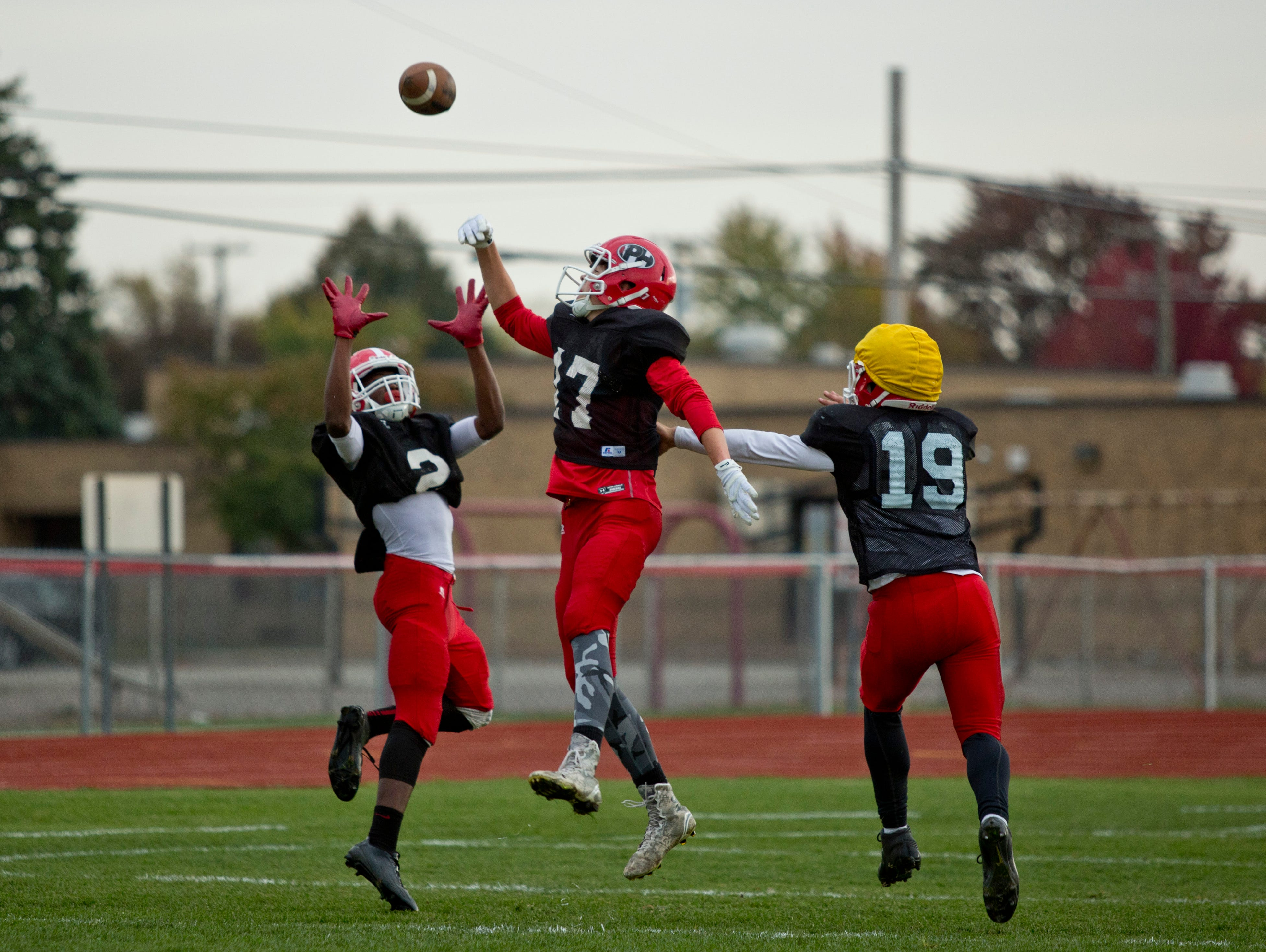 Port Huron's Javante Nichols leaps to catch a pass over Luke Winkler during practice Tuesday, October 20, 2015 at Port Huron High School.