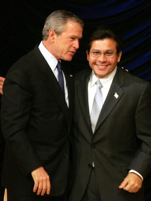 """Then-President George W. Bush embraces U.S. Attorney General Alberto Gonzales as he walks offstage after the Hispanic Chamber of Commerce in April 2005 in Washington, D.C. Gonzales has """"fond feelings"""" about his service."""