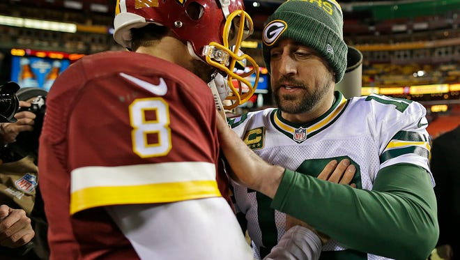 Green Bay Packers quarterback Aaron Rodgers (12) is congratulated by Washington Redskins quarterback Kirk Cousins (8) after Sunday's NFC wild-card round playoff game at FedEx Field in Landover, MD. The Packers defeated the Redskins 35-18.