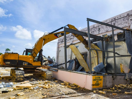 A worker operates a Catepillar excavator to take down