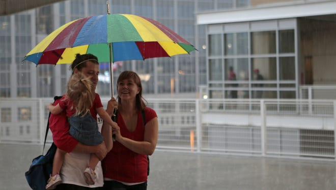 Zella Youtsey, 2; Bryan Youtsey 25; and Kryst Kruer, 25, of Covington, Kentucky, smile as they walk through the rain just before the game is called.