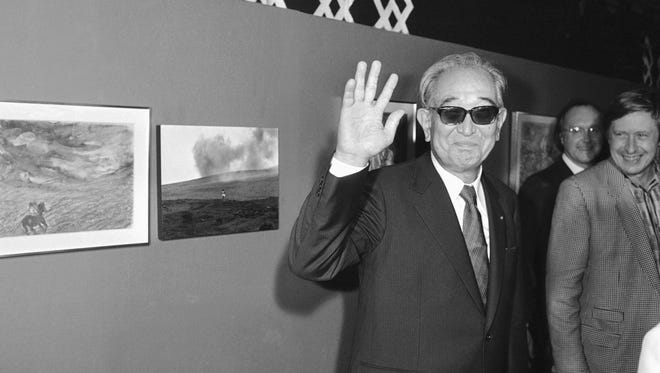 """Japanese movie director Akira Kurosawa salutes the photographers Thursday evening Sept. 19, 1985, when visiting the exhibition """"About Ran"""" held at Paris Georges Pompidou National Center for Art and Culture. """"About Ran"""" shows the costumes, pictures and drawings Kurosawa did for his film """"Ran."""" Visible at left is a picture of one of the shots of """"Ran."""""""