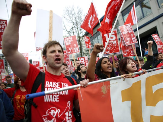 In this 2014 file photo, organizer Bryan Watson, left, gestures during a march to raise the minimum wage to $15 per hour in Seattle.