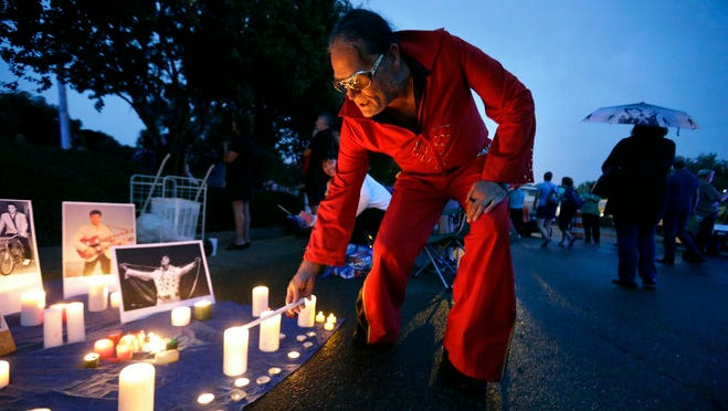 August 15, 2016- Elvis Whitney, of Denver, Colorado, lights his candle as a light rain begins to fall during Graceland's Elvis Candelight Vigil.