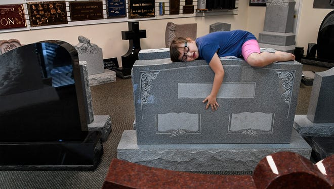 Braelyn Hardin hugs a headstone as her grandparents pick out a marker for their daughter Heather's grave April 14, 2018, at Schultz Monument Co. in Madison. Heather Baltz, Braelyn's mother, died Feb. 23 of a heart infection doctors believe originated with a contaminated needle used to shoot heroin.