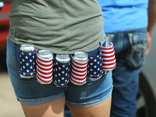 Country music fan Ashley Kessler keeps her beer handy