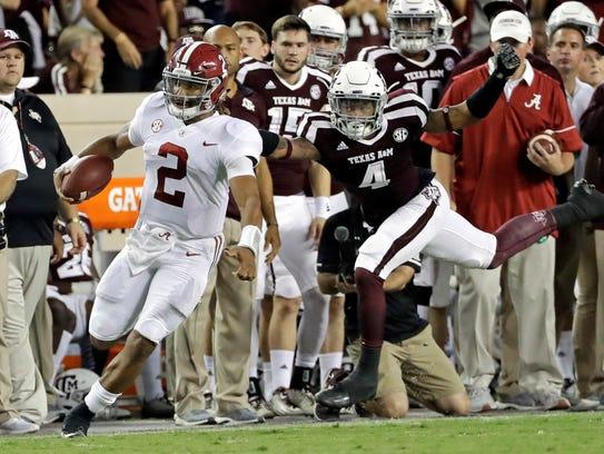 Alabama quarterback Jalen Hurts (2) rushes for a first
