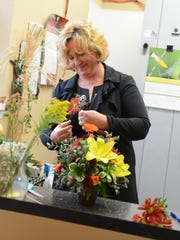 Audra Arebaugh prepares a flower arrangement at Audra's