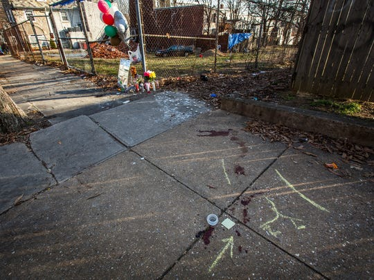 "Blood covers part of the sidewalk near a makeshift memorial for Samuel ""Sumo"" Copeland sits along West Seventh Street near Tilton Park on Tuesday afternoon."
