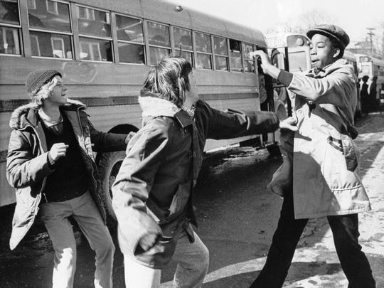 White and black students begin to fight outside Hyde Park High School in Boston, Mass., Feb. 14, 1975. The city of Boston started a court-ordered school integration program requiring the busing of 18 percent of public school students. (AP Photo/DPG)