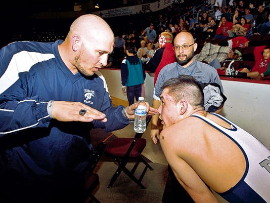 Piedra Vista head wrestling coach Levi Stout talks with Wyatt Weaver during the 4A State Wrestling Championship in February at the Santa Ana Star Center in Rio Rancho.