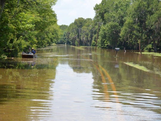 A boater (left) floats down La. Highway 1226 near the Allen Dam Community.